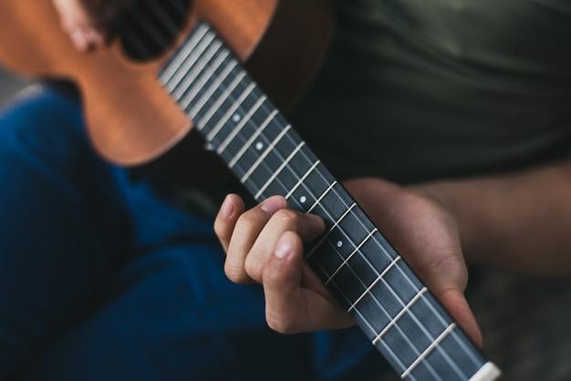 Jeu de ukulélé. un homme jouant un peu de guitare. l'interprète écrit la musique sur le ukulélé à la maison Photo Premium