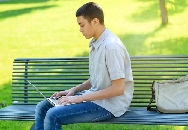 Jeune Adolescent à L'aide De Son Ordinateur Portable Dans Le Parc Photo Premium