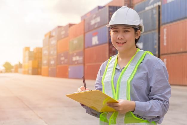 Jeune Adolescent Asiatique Travailleur Heureux Contrôle Des Stocks Dans Le Travail Du Port D'expédition Gérer Les Conteneurs De Fret Import Export Photo Premium