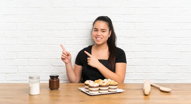 Jeune adolescente asiatique avec beaucoup de gâteau muffin doigt sur le côté Photo Premium