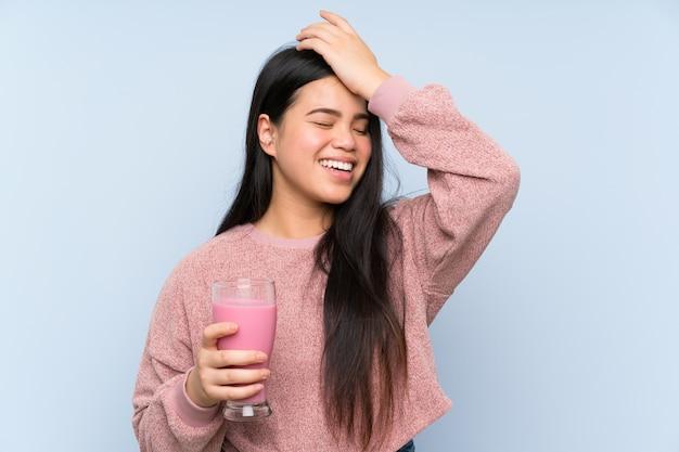 Jeune adolescente asiatique avec un milkshake à la fraise a réalisé quelque chose et a l'intention de la solution Photo Premium