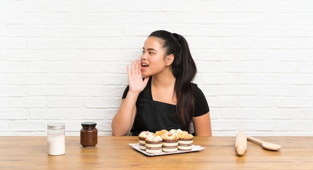 Jeune adolescente asiatique avec plein de muffins en criant avec la bouche grande ouverte Photo Premium