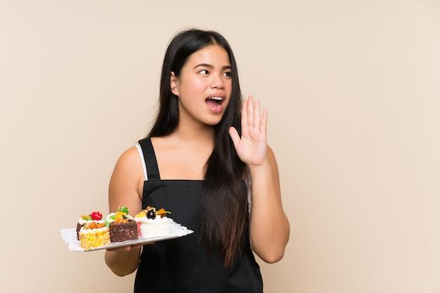 Jeune adolescente asiatique tenant beaucoup de mini-gâteaux différents sur un mur isolé criant avec la bouche grande ouverte Photo Premium