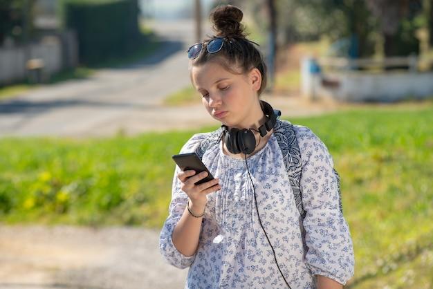 Jeune adolescente en attente du bus scolaire et utilisant son smartphone Photo Premium