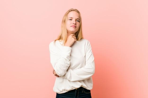 Une jeune adolescente blonde a mal à la gorge à cause d'un virus ou d'une infection. Photo Premium