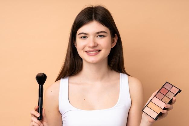 Jeune Adolescente Sur Mur Avec Palette De Maquillage Et Heureux Photo Premium