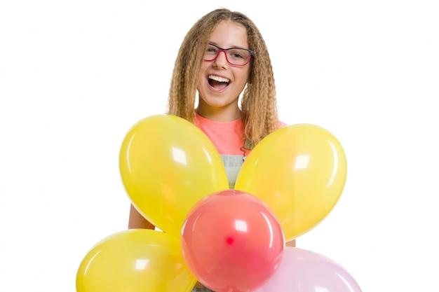 Jeune adolescente souriante avec des ballons de couleurs festives sur blanc isolé. Photo Premium