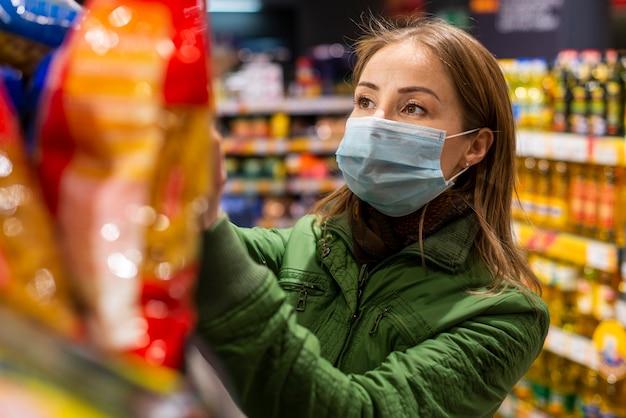 Jeune Adulte Portant Un Masque De Protection Et Achetant Des Produits Photo Premium