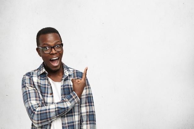 Jeune Afro-américain étonné Dans Des Verres Regardant La Caméra Avec La Bouche Ouverte Montrant Les Dents Photo gratuit