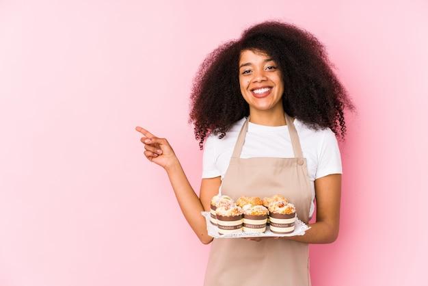 Jeune Afro Pâtissier Femme Tenant Un Cupcakes Isolé Jeune Femme Afro Boulangère Souriant Et Pointant De Côté, Montrant Quelque Chose à L'espace Vide. Photo Premium