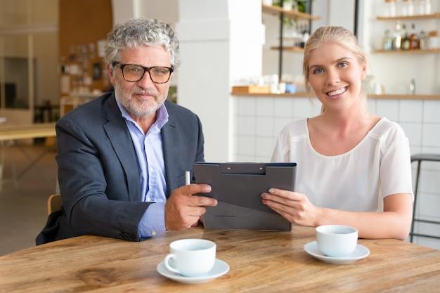 Jeune Agent Et Réunion Client Mature Sur Une Tasse De Café à Co-working, Assis à Table, Tenant Des Documents, Photo gratuit