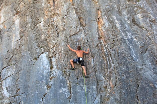 Jeune alpiniste grimpant sur le rocher sistiana, trieste Photo Premium
