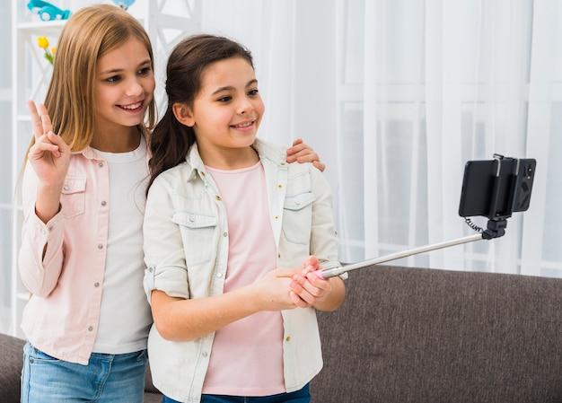 Jeune amie prenant une photo de selfie avec un bâton de selfie Photo gratuit