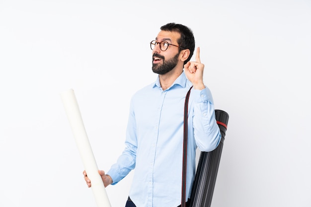 Jeune architecte homme à la barbe sur fond blanc isolé, pensant une idée pointant le doigt vers le haut Photo Premium