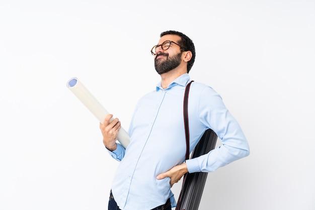 Jeune architecte homme à la barbe sur mur blanc isolé souffrant de maux de dos pour avoir fait un effort Photo Premium