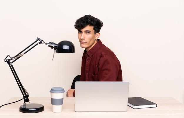 Jeune argentin assis à une table avec un ordinateur portable sur son lieu de travail en riant Photo Premium