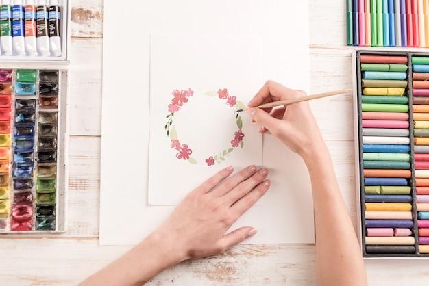 Jeune Artiste Dessin Motif De Fleurs Avec Peinture Aquarelle Et Pinceau Au Lieu De Travail Photo gratuit