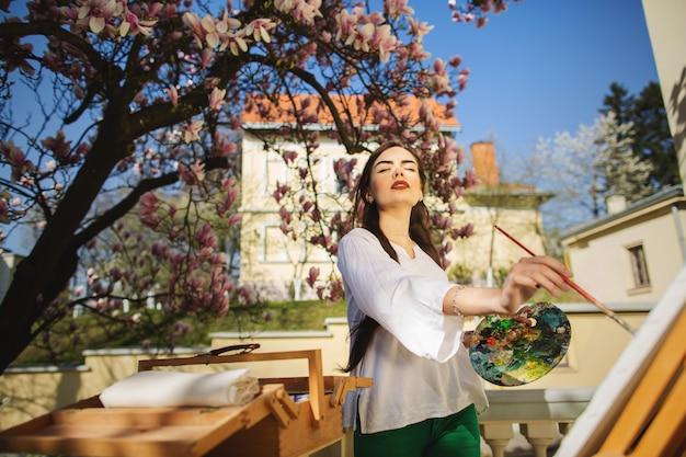 Jeune artiste femme brune tenant dans les mains un pinceau et une palette. Photo Premium