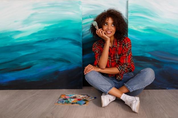 Un Jeune Artiste Femme Noire Souriante En Studio Tenant Un Pinceau. étudiante Inspirée Assise Sur Ses œuvres. Photo gratuit