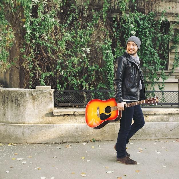 Jeune Artiste De Rue Attrayant Avec Sa Guitare Photo gratuit