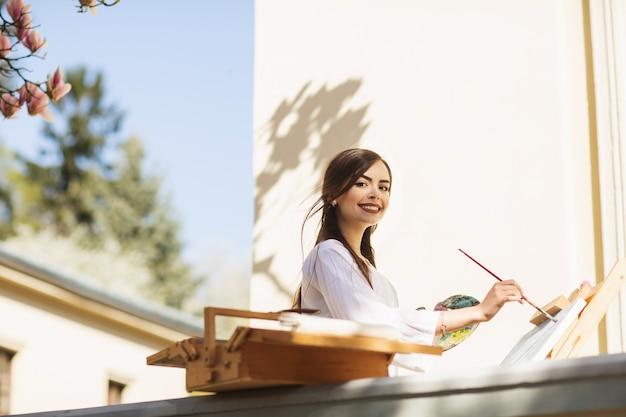 Jeune artiste souriante de femme brune dresse un tableau dans la rue Photo Premium