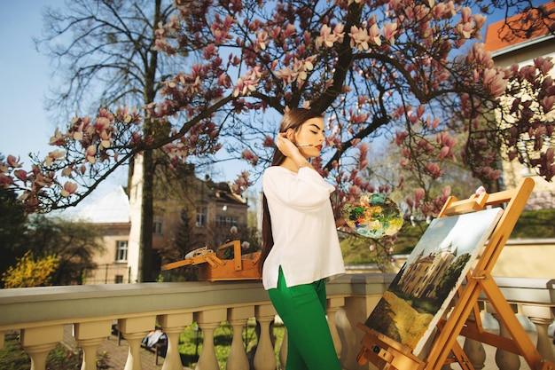 Jeune artiste souriante de femme brune peint une image dans la rue, près d'un bel arbre de magnolia Photo Premium
