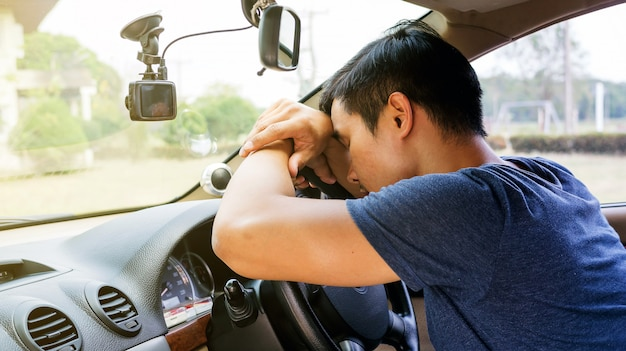 Jeune asiatique dort dans sa voiture. Photo Premium