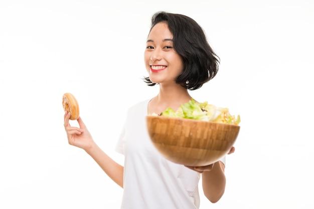 Jeune asiatique sur mur isolé avec salade et beignet Photo Premium