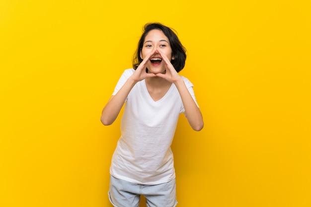 Jeune asiatique sur mur jaune isolé criant et annonçant quelque chose Photo Premium