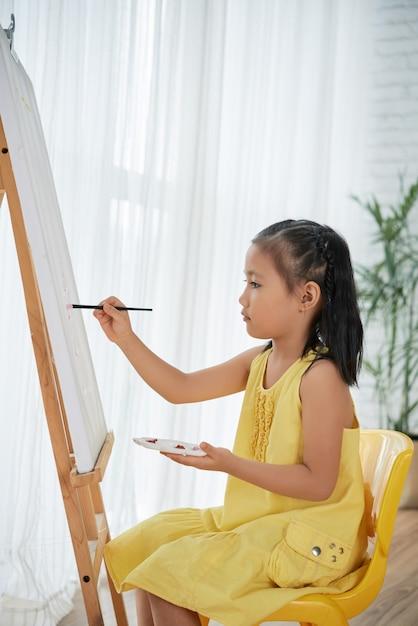 Jeune, asiatique, robe jaune, séance, devant, chevalet, chez soi, et, peinture Photo gratuit