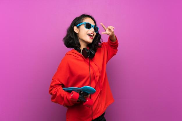 Jeune asiatique avec skate sur mur violet Photo Premium
