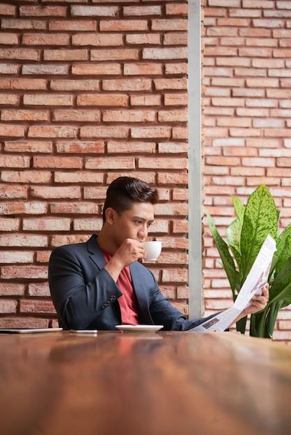 Jeune, asiatique, table, café mezzanine, café, lecture, journal Photo gratuit