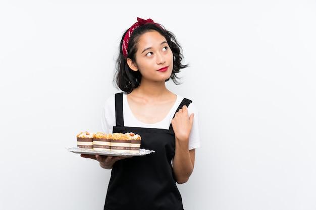 Jeune, Asiatique, Tenue, Beaucoup, Gâteau Muffin, Sur, Mur Blanc, Regarder, Tout, Sourire Photo Premium