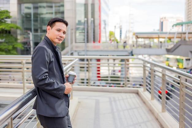 Jeune asie bel homme d'affaires, boire du café chaud dans la ville moderne Photo Premium