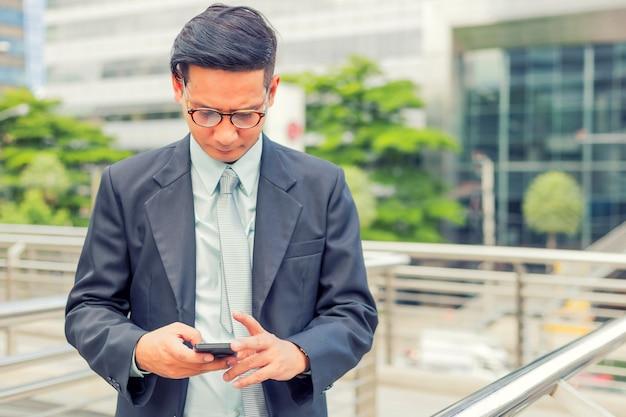 Jeune asie bel homme d'affaires avec son smartphone debout sur le trottoir de la ville moderne Photo Premium
