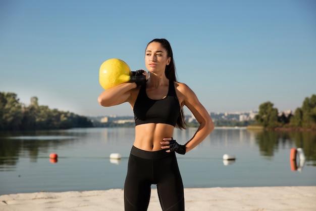 Jeune Athlète Féminine En Bonne Santé Faisant De L'exercice à La Plage Photo gratuit