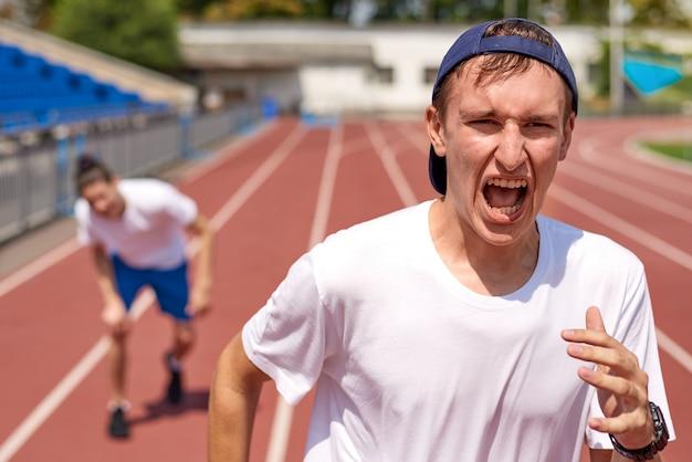 Jeune athlète homme sur piste de course avec l'adversaire Photo Premium