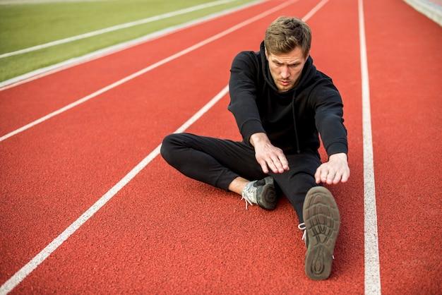 Jeune athlète masculin assis sur la piste de course qui s'étend de la main et des jambes Photo gratuit