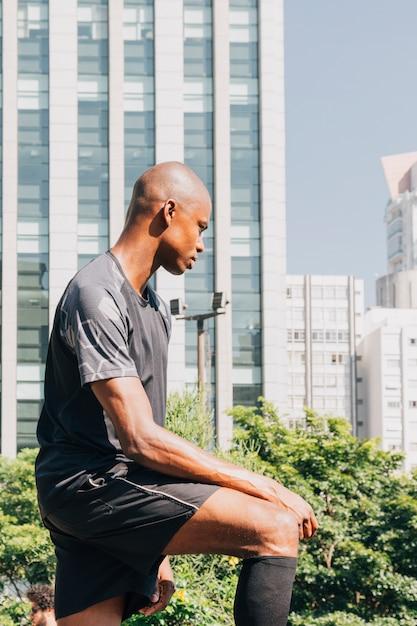 Jeune athlète masculin contemplé, debout devant le bâtiment Photo gratuit