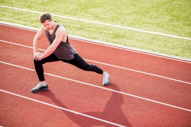 Jeune athlète masculin qui s'étend de son corps sur la piste de course Photo gratuit