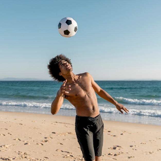 Jeune athlète noir jouant au ballon de foot sur la plage Photo gratuit