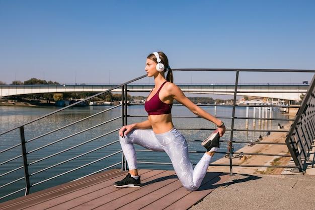 Jeune, athlétique, femme, écoute, musique, sur, casque, étirer, sa jambe, sur, pont Photo gratuit
