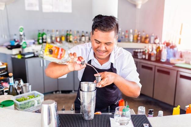 Jeune barman versant un cocktail dans un bar, phuket, thaïlande Photo Premium