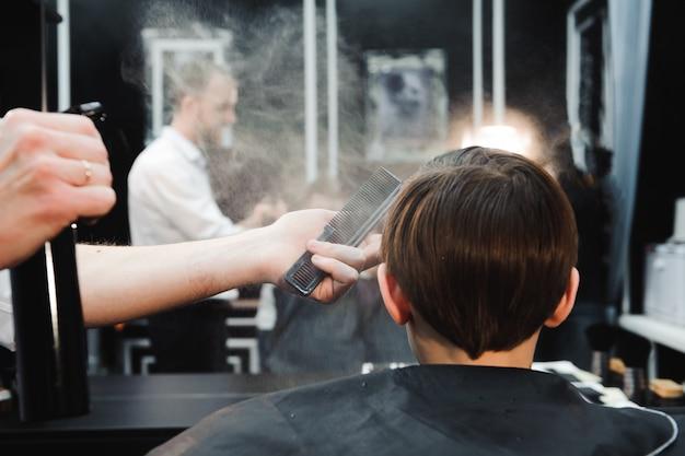 Jeune beau barbier faisant la coupe de cheveux de garçon dans le salon de coiffure Photo Premium