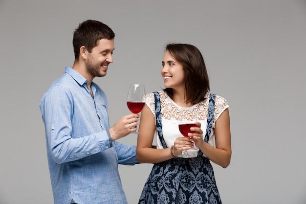 Jeune, Beau Couple, Boire Vin, Sourire, Sur, Mur Gris Photo gratuit