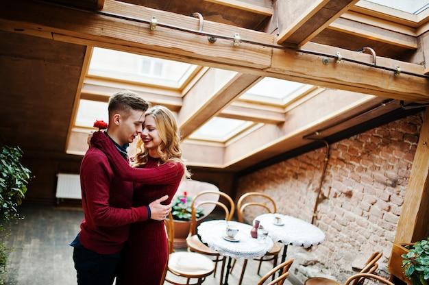 Jeune beau couple élégant dans une robe rouge dans l'histoire d'amour au café vintage avec de grandes fenêtres sur le toit Photo Premium