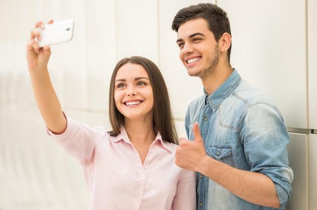 Jeune beau couple prenant selfie avec téléphone intelligent. Photo Premium