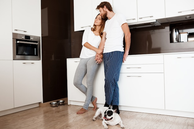 Jeune Beau Couple Souriant Debout à La Cuisine Avec Chien Carlin. Photo gratuit