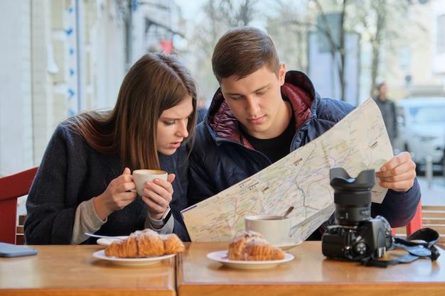 Jeune beau couple de touristes se reposant au café en plein air Photo Premium