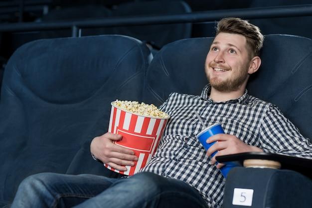 Jeune beau gai, appréciant un film au cinéma Photo Premium